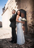 Bride and groom standing back to back and looking at camera at castle Stock Image