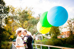 Bride and groom standing on the bridge with balloons Stock Photo