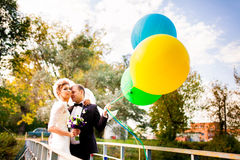 Bride and groom standing on the bridge with balloons Stock Photos