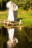Bride and groom are standing on a bridge near the forest Royalty Free Stock Photography