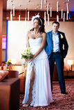 Bride and groom are standing in a bright room Stock Photos