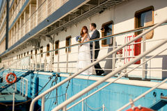 Bride and groom standing on cruise ship deck at sunset Stock Image