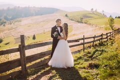 Bride and groom standing embracing near wooden fence on the road background Royalty Free Stock Photography