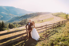 Bride and groom standing embracing near wooden fence on the road background Stock Images
