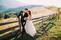 Bride and groom standing embracing near wooden fence on the road background Royalty Free Stock Photo