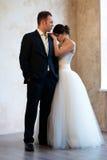 Bride and groom standing in empty room Stock Photos