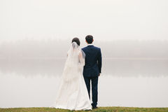 Bride and groom standing in front of lake  looking far Stock Photo