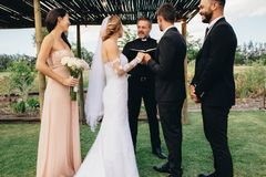 Outdoor wedding ceremony of beautiful couple. Bride and groom standing in front of priest witness by bridesmaids and best man. Outdoor wedding ceremony of royalty free stock image