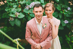 Bride and groom standing near bush with flowers Royalty Free Stock Photos