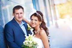 Bride and groom is standing near the granite wall Stock Photo