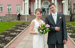 Bride and groom standing near registry office Royalty Free Stock Photography