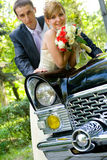Bride and groom standing near wedding car Royalty Free Stock Image