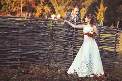 Bride and groom standing near the wicker fence. In autumn park and looking at each other Royalty Free Stock Photography