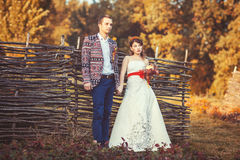 Bride and groom standing near the wicker fence holding hands. And look far away Royalty Free Stock Images