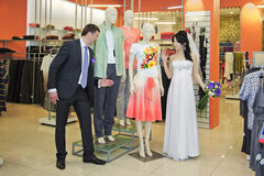 Bride and groom standing in a shop near dummy Royalty Free Stock Photography