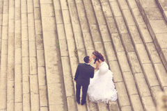 Bride and groom standing on stairs Royalty Free Stock Photos