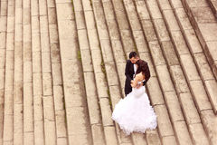 Bride and groom standing on stairs Stock Photo