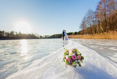 Bride and groom are standing at the surface of frozen lake Stock Photo
