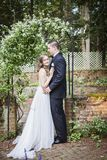 Bride and Groom  portrait in garden. A bride and groom standing under arch on brick patio  in garden Stock Image