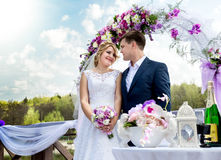 Bride and groom standing under floral arch at sunny day Royalty Free Stock Photos