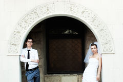 Bride and groom standing under white arch Stock Photography