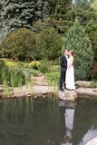 Bride and groom standing at the water Stock Photography