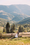 The bride and groom standing on wooden bridge in nature, embracing near fence with mountain background Royalty Free Stock Photography