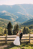 The bride and groom standing on wooden bridge in nature, embracing near fence with mountain background Royalty Free Stock Photo