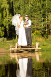 The bride and groom are standing on a wooden bridge Royalty Free Stock Photo