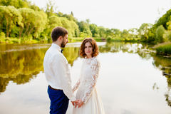 The bride and groom are standing on a wooden pier near the pond Royalty Free Stock Photo