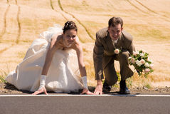 Bride and groom on starting line. Bride and groom are crouched on starting line and ready for their new life. Golden field is used as background, groom is royalty free stock photos