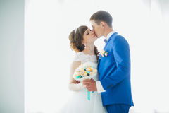 Bride and groom in studio light stand  kiss on a white background Stock Images