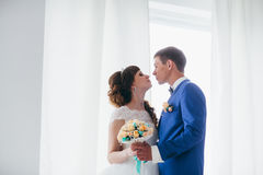Bride and groom in studio light stand kiss on a white background Stock Photo