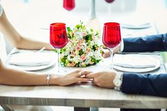 Bride and groom in a suit sitting at served table, served table for the bride and groom, wedding decor and serving, wedding flower Royalty Free Stock Image