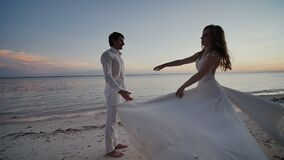 The bride and groom at sunset on a beautiful tropical beach. The bride sensually dances before the groom, holding on to stock video