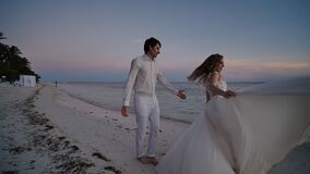 The bride and groom at sunset on a beautiful tropical beach. The bride sensually dances before the groom, holding on to stock video footage