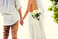 Bride and groom at sunset on tropical beach Stock Photos