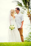 Bride and groom at sunset on tropical beach Stock Image