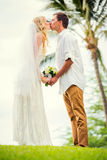 Bride and groom at sunset on tropical beach Royalty Free Stock Photography