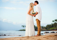 Bride and groom at sunset on tropical beach Royalty Free Stock Photos