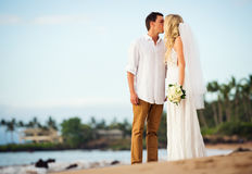 Bride and groom at sunset on tropical beach Stock Photo