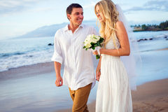 Bride and groom at sunset on tropical beach Stock Images