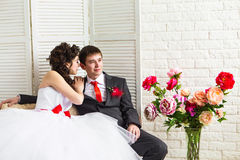 Bride and groom surrounded by flowers Stock Photography