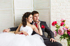 Bride and groom surrounded by flowers Stock Photos