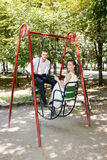 Bride and groom on a swing. Happy bride and groom swinging on a swing Stock Image
