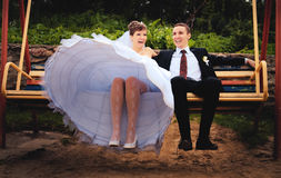 Bride and groom swing on a swing Royalty Free Stock Photography