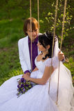 Bride and groom swinging on a swing Stock Photos