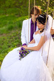 Bride and groom swinging on a swing Royalty Free Stock Image