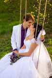 Bride and groom swinging on a swing Stock Photo