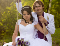 Bride and groom swinging on a swing Stock Image